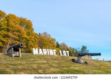 """The marine section of a cemetery. Two canon and an anchor next to large letters that spell """"MARINE LOT"""". No grave markers are visible. Sunny day with pale blue sky."""