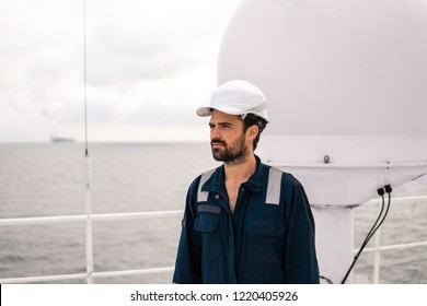 Marine service technician or serviceman near VSAT terminal on deck of vessel or ship