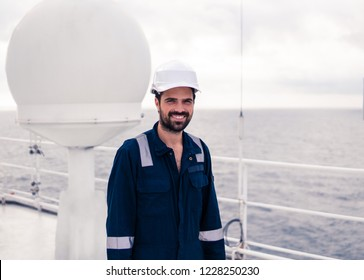 Marine service technician or serviceman near VSAT terminal on deck of vessel or ship. He is smiling