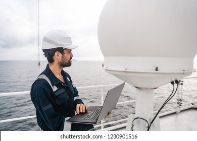 Marine service technician or serviceman near VSAT terminal on deck of vessel or ship. He is working on laptop or notebook