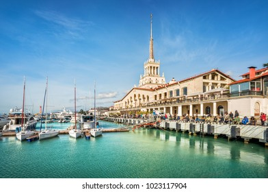 Marine Station on the shore of the emerald Black Sea in Sochi on a sunny day under the blue sky, white yachts and fishermen on the shore