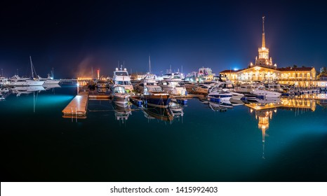 Marine Station of Sochi, illuminated with lights at night with reflection in water. Yachts and boats at the pier. Translation of the inscription above the central entrance to the building means Sochi