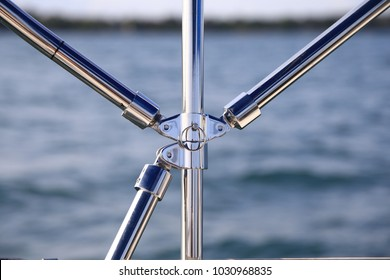 Marine steel railings on a boat on a bright sunny day with blue water and sky in the background.