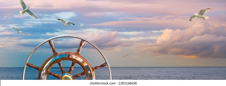 Marine sunrise in pastel colors with a steering wheel of skipper. Serenity landscape with a cloudy sky and seagulls for your background about romantic sea cruise on a ship around the world, wide shot.