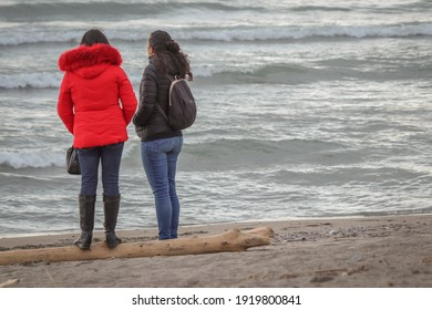 Marinella di Sarzana, La Spezia Italy - February 18 2021: young women chatting on the winter beach during the pandemic.