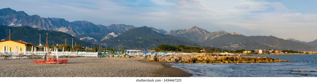 MARINELLA, MASSA CARRARA, ITALY – JUNE 20, 2019: Quiet evening on the beach at Marinella, Massa Carrara, Italy. The Lifeguard station is deserted. The Apuan Alps can be seen in the distance.