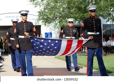 Marines carrying flag at Memorial Day ceremony