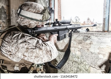 Marines sniper armed with large caliber, anti-materiel sniper rifle hiding in ruined urban building, shooting enemy targets on range from shelter, sitting in ambush. Military firefight in city