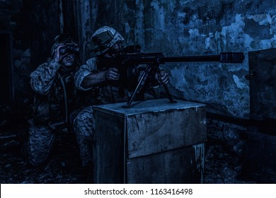 Marines sniper team armed with large caliber, anti-materiel sniper rifle hiding in ruined urban building, shooting enemy targets on range from shelter, sitting in ambush at night. Military firefight