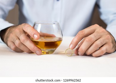 Marital problems. The hands of a man sitting at a white table are holding a glass of whiskey. The other hand is holding a wedding ring.