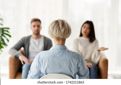 Marital Therapy. Professional Psychologist Sitting Back To Camera During Appointment With Unhappy Couple In Office. Rear View, Selective Focus