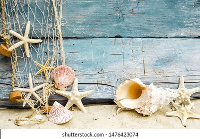 Maritim souvenir from holidays on the beach: Seashell background border on rustic blue wood. Top view on different seashells and starships with white sand and fishnet.