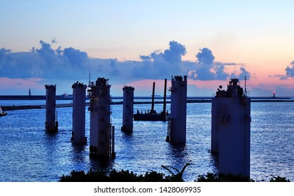 A maritime construction project with large pylons at sunset