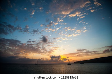 Maritime landscape at dawn with some boats in the background and an expressive sky with clouds