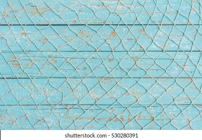 Maritime nautical fishing net texture on turquoise blue wood background, copy space.