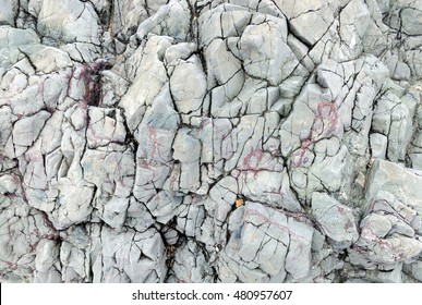 Maritime rock textured with pink veins, deep cracks, and shades of grey along the coast of Llanddwyn Island, Anglesey, Wales.