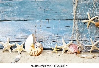 SeemannsSouvenirs aus Feiertagen am Strand: Muschelhintergrund auf rustikalem blauem Holz. Blick auf verschiedene Sternschiffe und Muscheln mit weißem Sand und Fischnetz.