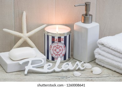 maritime spa still life with nautical candle, soap, towels seashells and word relax