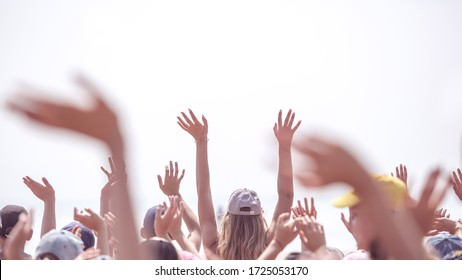 Mariupol, Ukraine - 25 June 2019: Group of happy young people with hands up to the sky near sea