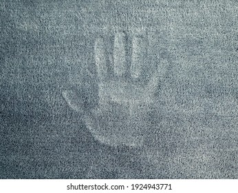 Mark of the hand on the grey velour textured surface. Palm silhouette. Concept of ghostly vision, phantom