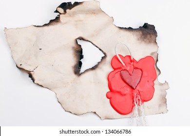 mark in the shape of a heart made of red wax on a piece of burnt paper