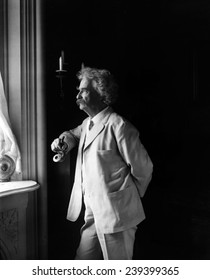 Mark Twain (Samuel L. Clemens, 1835-1910) American humorist standing by window in 1907 portrait.