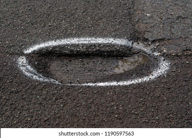Marked pothole in a road.