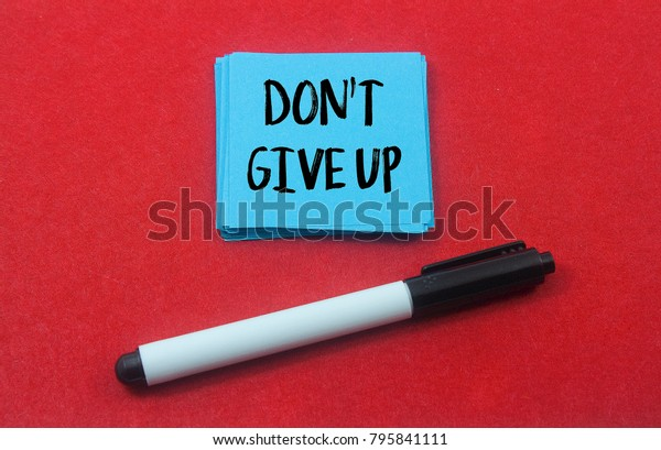 marker pen and paper note written don't give up over red background