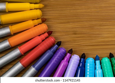 Markers Alternating between Tips and Caps in a quarter circle design on a bamboo table with room on the top right for copy work.  Arranged in the order of the color wheel.
