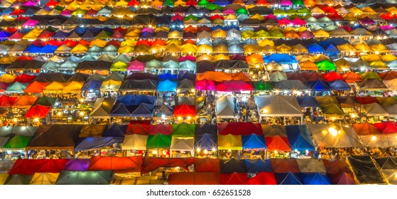 Market with colorful tents in night time. This is place in Thailand call Train Market. It is big market with a lot of foods and crowd people. Photo show top view of market. You may spend nightlife.