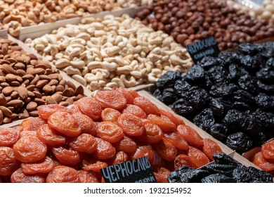 Market counter with various assorted dried fruits and nuts. Healthy food. Local market.translation: prunes, dried apricots, cashews, hazelnuts.