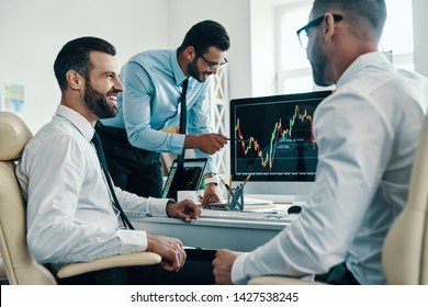 Market is growing. Group of young modern men in formalwear analyzing stock market data while working in the office