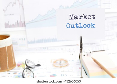 Market outlook : investment overview  message on the photo holder with background of  stationary, money, compass,  and stock chart