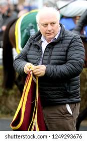 MARKET RASEN RACECOURSE, LINCOLNSHIRE, UK : 22 NOVEMBER 2018 : Racehorse Trainer Peter Bowen folds a horse rug up at Market Rasen Races