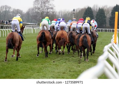 MARKET RASEN RACECOURSE, LINCOLNSHIRE, UK : 26 DECEMBER 2018 : Rear view of the Racehorses and their jockeys galloping down the track at Market Rasen Races