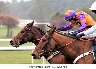 MARKET RASEN RACECOURSE, LINCOLNSHIRE, UK : 26 DECEMBER 2018 : Two racehorses and their jockeys go head to head in a photo finish at Market Rasen Races