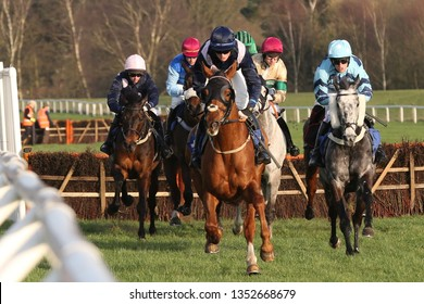 MARKET RASEN RACECOURSE, LINCOLNSHIRE, UK : 20 MARCH 2019 : Racehorses gallop down the home straight after jumping a hurdle at Market Rasen Races - head on view
