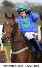 MARKET RASEN RACECOURSE, LINCOLNSHIRE, UK : 3 APRIL 2019 : Jockey Harry Skelton adjusts his chin strap on board Global Domination before racing at Market Rasen Races