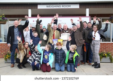MARKET RASEN RACECOURSE, LINCOLNSHIRE, UK : 3 APRIL 2019 : A large syndicate group of Winning Owners celebrate during the Presentation on the Winners Podium At Market Rasen Races