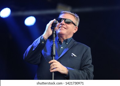 MARKET RASEN RACECOURSE, LINCOLNSHIRE, UK : 7 JUNE 2019 : Singer Songwriter and frontman Suggs for Ska Band Madness performs live on stage with the band at Market Rasen Racecourse