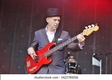 MARKET RASEN RACECOURSE, LINCOLNSHIRE, UK : 7 JUNE 2019 : Mark Bedford the Bass guitarist of popular Ska Band Madness performs live on stage at Market Rasen Racecourse