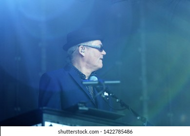 MARKET RASEN RACECOURSE, LINCOLNSHIRE, UK : 7 JUNE 2019 : Mike Barson keyboard player with Ska group Madness plays live on stage at Market Rasen Racecourse