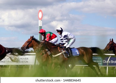 MARKET RASEN RACECOURSE, LINCOLNSHIRE, UK : 21 JUNE 2019 : Racehorses galloping past the Winning Post during a race at Market Rasen Races - taken from ground camera in grass for soft focus and blur