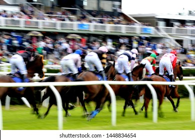 MARKET RASEN RACECOURSE, LINCOLNSHIRE, UK : 21 JUNE 2019 : Racehorses set off on a 2m 4f steeplechase race in front of the Grandstands at Market Rasen Races - camera pan with slow shutter speed