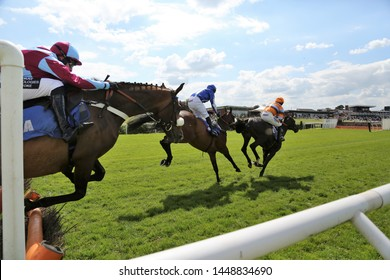 MARKET RASEN RACECOURSE, LINCOLNSHIRE, UK : 21 JUNE 2019 : Racehorses jump the last hurdle fence during racing at Market Rasen Races