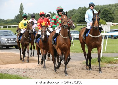 MARKET RASEN RACECOURSE, LINCOLNSHIRE, UK : 7 JULY 2019 : Jockeys and racehorses walk on to the track before racing at Market Rasen Races