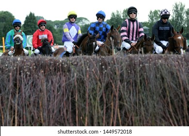 MARKET RASEN RACECOURSE, LINCOLNSHIRE, UK : 7 JULY 2019 : Jockeys and racehorses circling at the start of a race at Market Rasen Races - view from inside steeplechase fence
