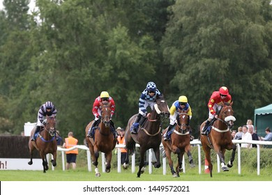 MARKET RASEN RACECOURSE, LINCOLNSHIRE, UK : 7 JULY 2019 : Racehorses galloping towards a steeplechase fence in the home straight whilst racing at Market Rasen