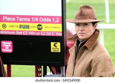 MARKET RASEN RACECOURSE, MARKET RASEN, LINCOLNSHIRE, UK : 20 JULY 2019 : An attractive lady bookmaker wears a trilby hat as she stands next to her Odds Board during Market Rasen Ladies Day