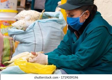 Market seller cleans corn in respiratory mask during coronavirus pandemic in Cusco, Peru in Latin South America. Epidemic of coronavirus covid-19